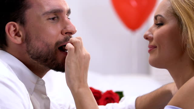 woman seducing man with chocolates, kissing with love, romantic atmosphere - temptation stock videos & royalty-free footage