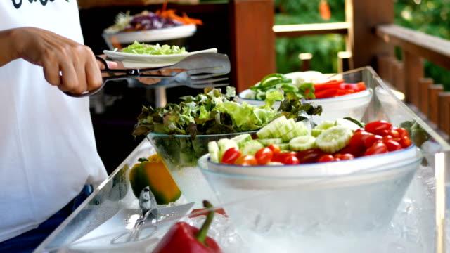 4k. kadın salata gıda, vejetaryen için renkli meyve ve sebze ile otel restoranda catering açık büfe gıda farklı organik sebze seçin. diyet sağlık sağlıklı yaşam tarzı - gıda ve i̇çecek sanayi stok videoları ve detay görüntü çekimi