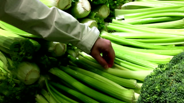 Woman selecting celery in grocery store video