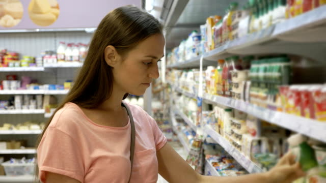 Woman selecting dairy products in fridge at grocery department of shopping mall video