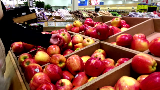 Woman selecting gala apple in grocery store