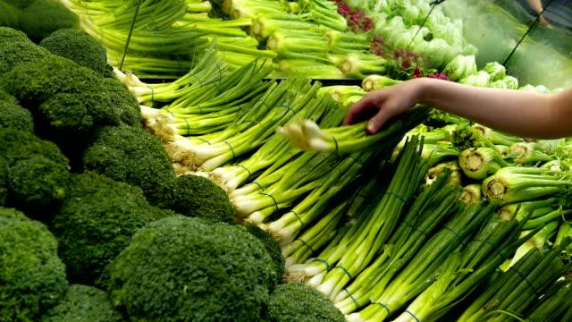 donna selezione di cipolle verdi in un negozio di alimentari - broccolo video stock e b–roll