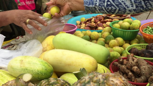 woman selecting lime in market - video di bancarella video stock e b–roll