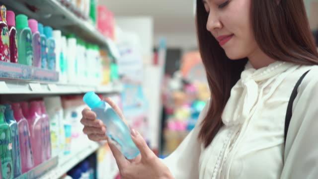 Mujer selecciona productos en los estantes de la tienda - vídeo