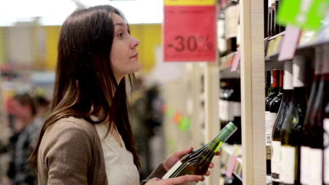 Woman selects the wine on the shelves in the store video