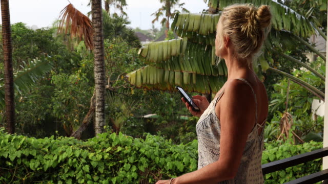 Woman sends text on smart phone, in tropical setting video