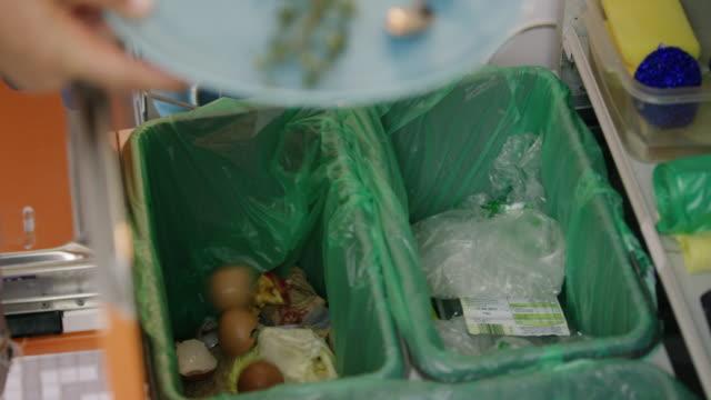 vídeos de stock e filmes b-roll de woman separating organic waste, plastic and paper into bins - economia circular