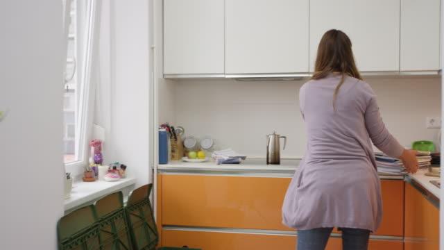 vídeos de stock e filmes b-roll de woman separating plastic and paper into bins - economia circular
