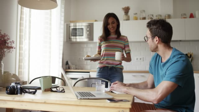 Woman serving breakfast while discussing with man