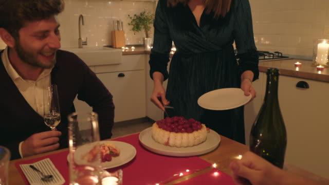 mum ışığında masada arkadaşlarına pasta hizmet veren kadın. - kek dilimi stok videoları ve detay görüntü çekimi