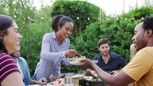 vidéos et rushes de femme servant le groupe des amis multiculturels à la maison à la table appréciant la nourriture à la partie de jardin d'été - barbecue