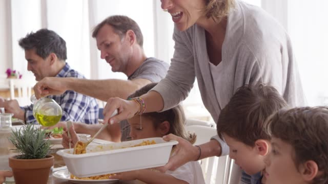Woman Serving Pasta To Children In Lunch At Table