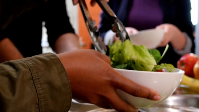 Woman serving salad to diverse group of friends during dinner party
