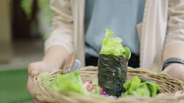 Woman serving Vegan homemade seaweed roll in wicker basket