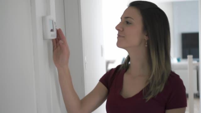 bir kadın evde termostatı ayarladı. - ayarlamak stok videoları ve detay görüntü çekimi