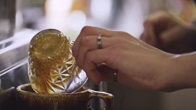 eine frau sets unten gedämpfte milch wischt ihr espresso-maschine und gießt schuss espresso in eine tasse kaffee - cappuccino stock-videos und b-roll-filmmaterial