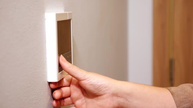 frau setzt thermostat drücken tasten in komfortablen hotel - medizinisches untersuchungsgerät stock-videos und b-roll-filmmaterial
