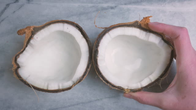 Woman Setting Up and Coconut Flat Lay on a Marble Table in 4k video