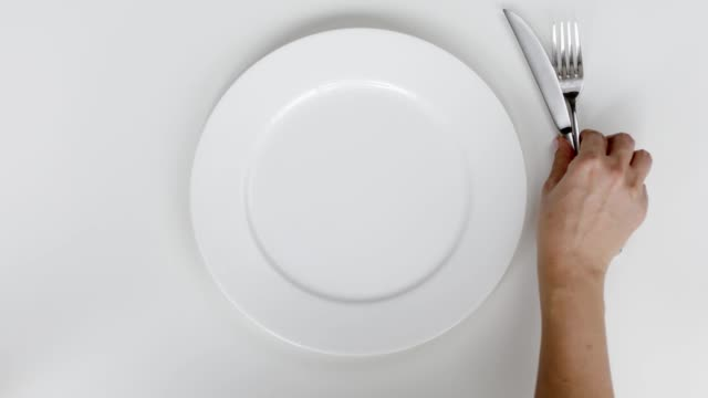 Woman setting up table, a plate and cutlery for meal
