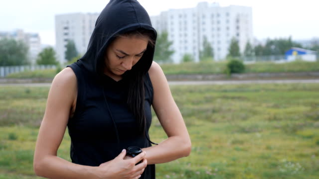 Woman setting up the fitness smartwatch for running. Sporty girl checking watch device.