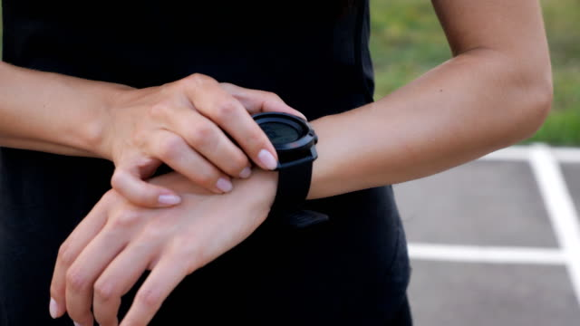 Woman setting up the fitness smartwatch for running. Sporty girl checking watch device, close up.