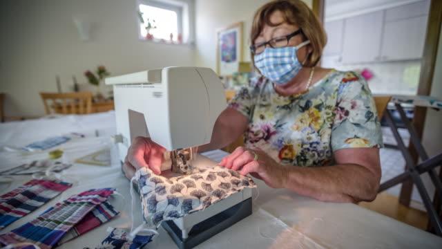 vidéos et rushes de femme cousant un masque protecteur anti-virus fait maison - coudre