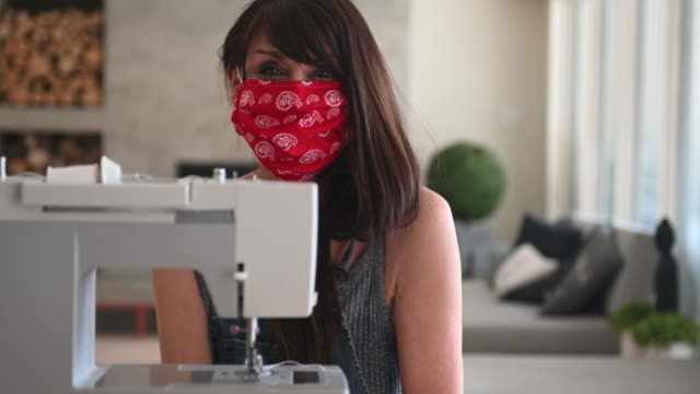 woman sewing covid-19 masks at home - cucire video stock e b–roll