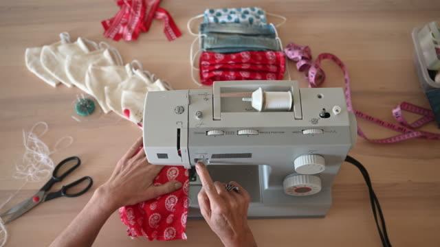 woman sewing covid-19 masks at home - sztuka i rzemiosło wytworzony przedmiot filmów i materiałów b-roll