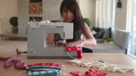 istock Woman sewing Covid-19 masks at home 1218405991