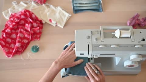 vídeos de stock e filmes b-roll de woman sewing covid-19 masks at home - feito em casa