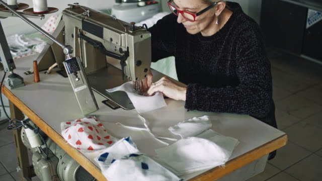 slo mo woman sewing fabric to make homemade masks - face mask stock videos & royalty-free footage