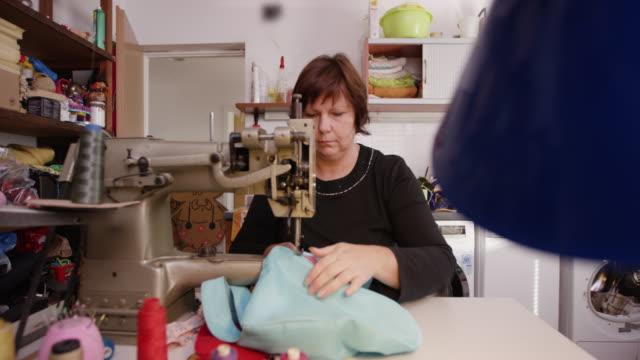 vídeos de stock e filmes b-roll de woman sewing pattern onto bag - economia circular