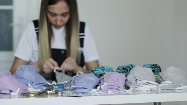 vidéos et rushes de la femme coud des masques médicaux. une jeune couturière prépare des équipements de protection pour les hôpitaux. - coudre
