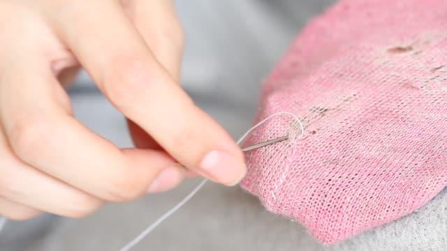 vídeos y material grabado en eventos de stock de la mujer cose agujeros en calcetines rosados. costura hecha a mano. pobreza y concepto mendí. - social media