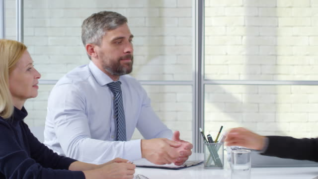 Woman Shaking Hands with Businesspeople during Job Interview