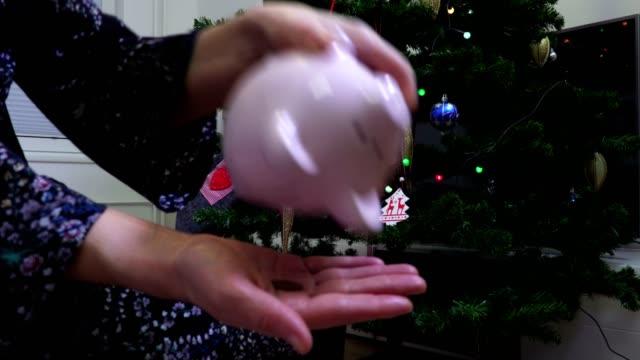vídeos y material grabado en eventos de stock de mujer sacudiendo rosa hucha cerca de árbol de navidad - accesorio financiero