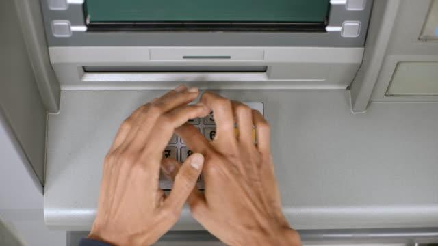 vídeos de stock, filmes e b-roll de mulher de ld blindagem o teclado sobre o atm como ela entra em seu número pin - pin