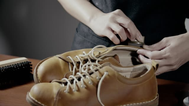 Woman shoe shiner polishes the boots of brown leather with brush