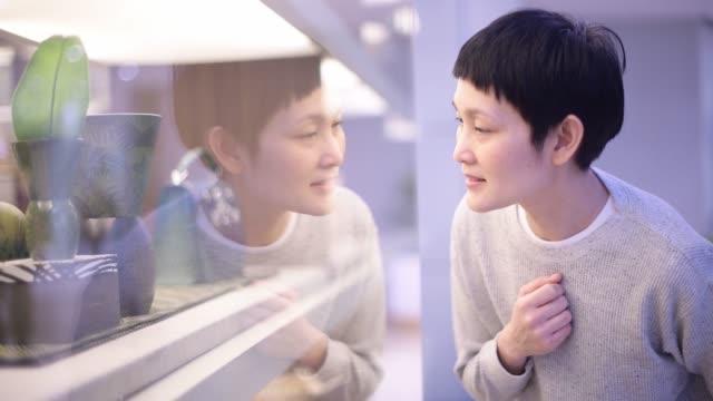 frau kauft im einkaufszentrum ein. asiatische dame mit glücklichem gesicht im kaufhaus - schaufenster stock-videos und b-roll-filmmaterial