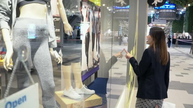 Mujer de compras por las tiendas por menor en cámara lenta. - vídeo