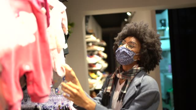 Woman shopping for baby clothes and protecting herself wearing protective mask
