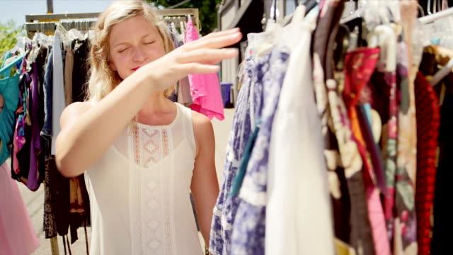 vídeos de stock, filmes e b-roll de mulher compras de roupas em um mercado ao ar livre - arméria