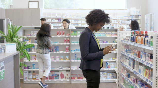 Woman shopping for medicine at drug store A young black woman is at the pharmacy. She is selecting over the counter medicine. The woman is standing in the aisle of the store, reading the labels on medication. Pharmacists are assisting customers in the background. pharmacy stock videos & royalty-free footage