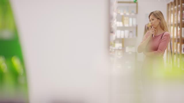 vídeos de stock, filmes e b-roll de mulher que compra produtos do skincare na loja cosmética - skincare