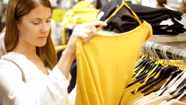 Woman shopping in mall. Standing near shelves with clothes choosing pullover. Picking up yellow jersey video
