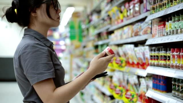 woman shopping in supermaket - dagligvaruhandel, hylla, bakgrund, blurred bildbanksvideor och videomaterial från bakom kulisserna