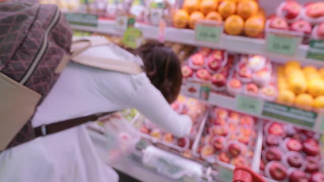 vídeos y material grabado en eventos de stock de mujer de compras en el supermercado en el centro comercial - snack aisle