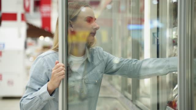 frau einkaufen im supermarkt wahl gefrorene produkte im kühlschrank - etikett stock-videos und b-roll-filmmaterial