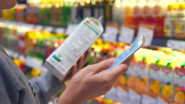 frau kauft im supermarkt mit smartphone ein - etikett stock-videos und b-roll-filmmaterial