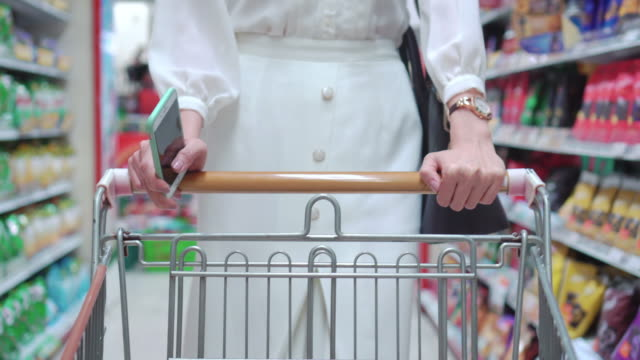 woman shopping in supermarket,steadicam shot - retail worker stock videos and b-roll footage